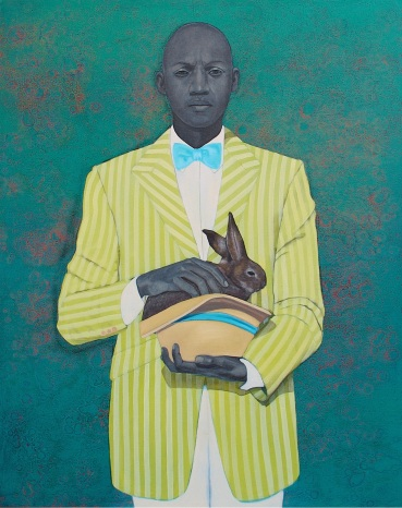 Portrait of a man with a bunny in his hands and a striped yellow jacket.