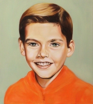 Portrait of a smiling boy with an orange shirt.