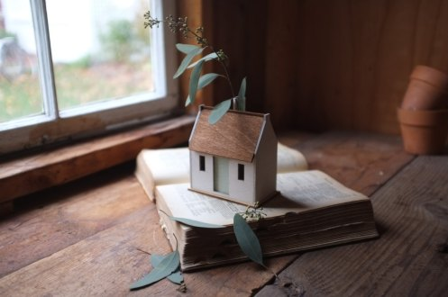 Still life of a tiny cottage putted over a book.