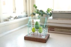Still life of a miniature greenhouse structure.