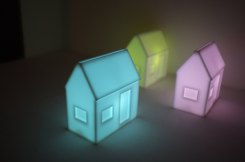 Still life photo of 3 miniature neon acrylics houses.