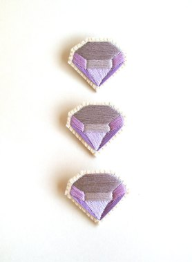 Trio of purple diamond shaped brooches.