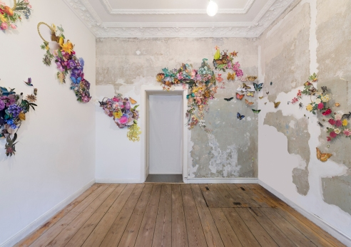 Overview of a collage installation made of paper into a room.