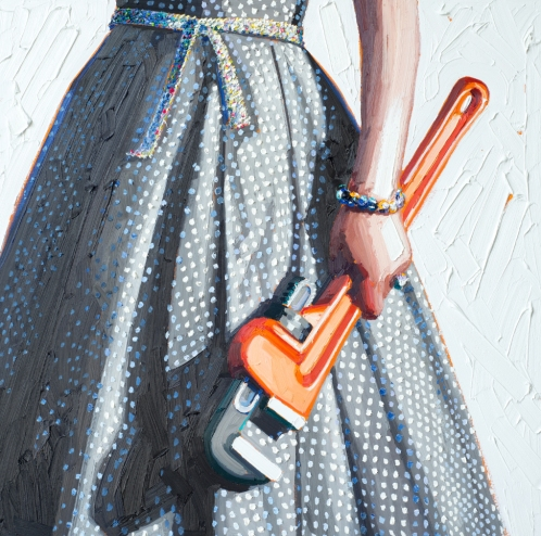 Woman torso wearing a dotty dress and holding a wrench