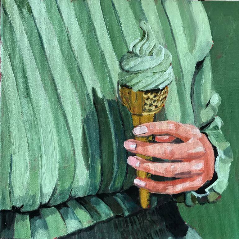 Female hand holding a green gelato cone dressed in green.