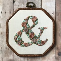 Still life photo of an hand embroidered ampersand on textile surface.