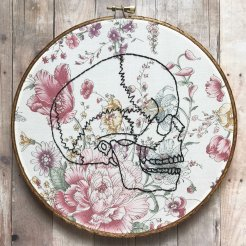 Still life photo of an hand embroidered skull over a floral textile.