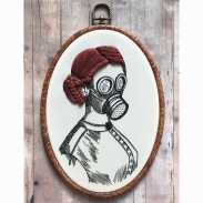 Still life photo of an hand embroidered woman bust with a gas mask.