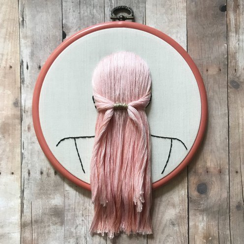 Still life photo of an hand embroidered back female head with pink hair.