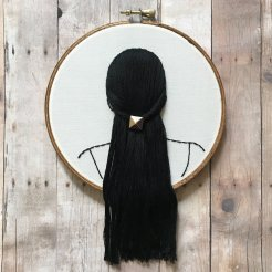 Still life photo of an hand embroidered back female head with black hair.