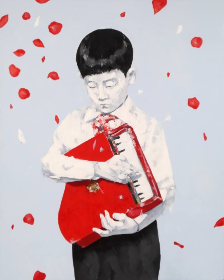 Portait of a young boy holding a mini piano.