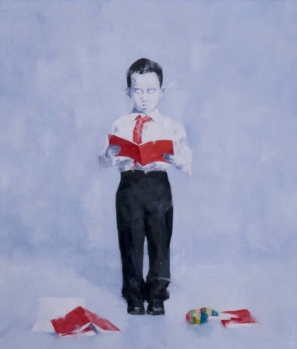 Portrait of a young boy reading a red book.