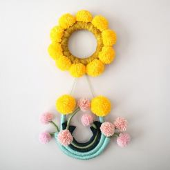Still life of a fiber art sculpture composed by a circular yellow piece and another piece that simulates flowers made of pom poms.