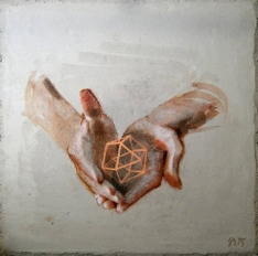 Hands holding a geometric element.
