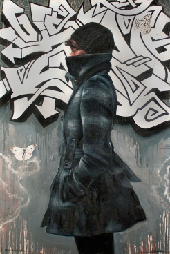 Profile portrait of a woman in front of a graffiti wall.