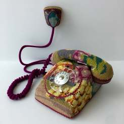 Still life photo of a telephone entirely covered with a textile.