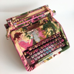Still life photo of a typewriter entirely covered with a textile.