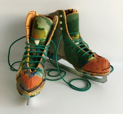 Still life photo of ice skating shoes entirely covered with a textile.