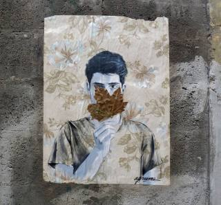 Man portrait that is covering his face with a leaf.