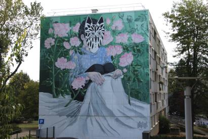 Mural on a wall of a masked man surrounded by flowers.