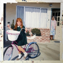 Smiling girl riding a bike portrait.