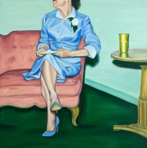 Elegant woman wearing a blue dress sit on a couch portrait.